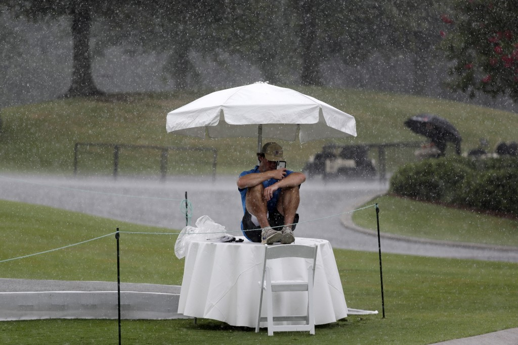 Security worker Raymond Fracchia takes shelter under an umbrella as rain falls during a practice round at the World Golf Championship-FedEx St. Jude I...