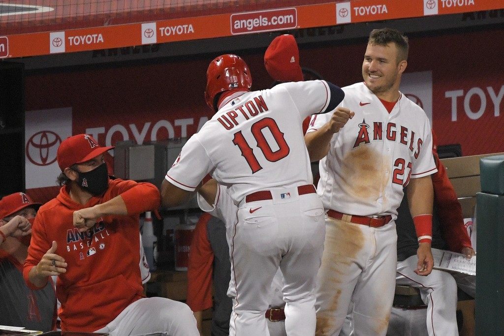 Los Angeles Angels' Justin Upton, center, is congratulated by teammates, including Mike Trout, right, after hitting a solo home run during the sixth i...