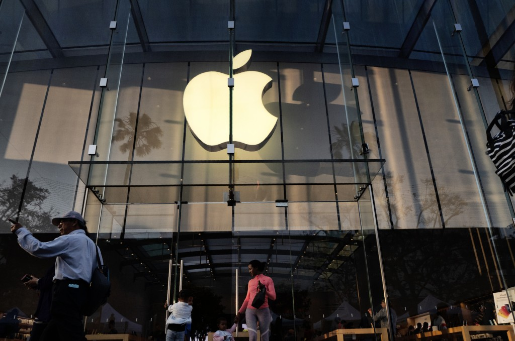 FILE - In this June 15, 2019, file photo customers leave an Apple store on the 3rd Street Promenade in Santa Monica, Calif.  Big Tech companies report...