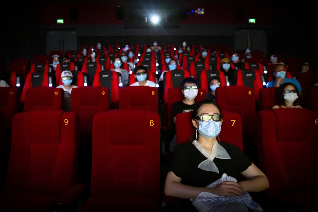 """People wearing face masks to protect against the coronavirus sit spaced apart as they watch the film """"Dolittle"""" at a movie theater in Beijing, Friday,..."""