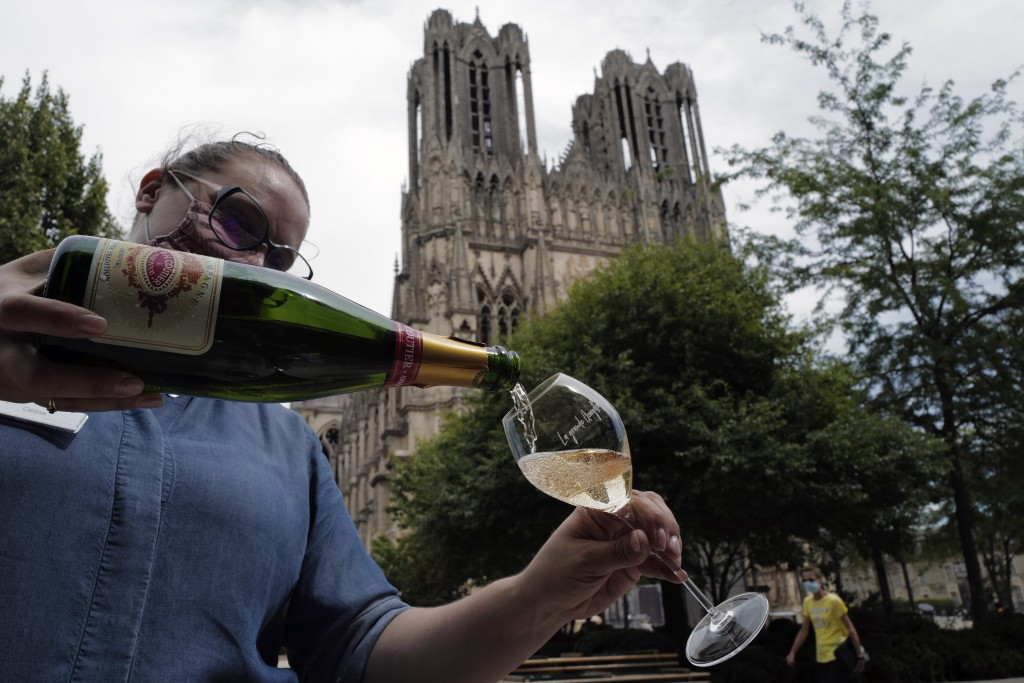 A waitress serves a glass of champagne at La Grande Georgette restaurant in front of the cathedral in Reims, the Champagne region, east of Paris, Tues...