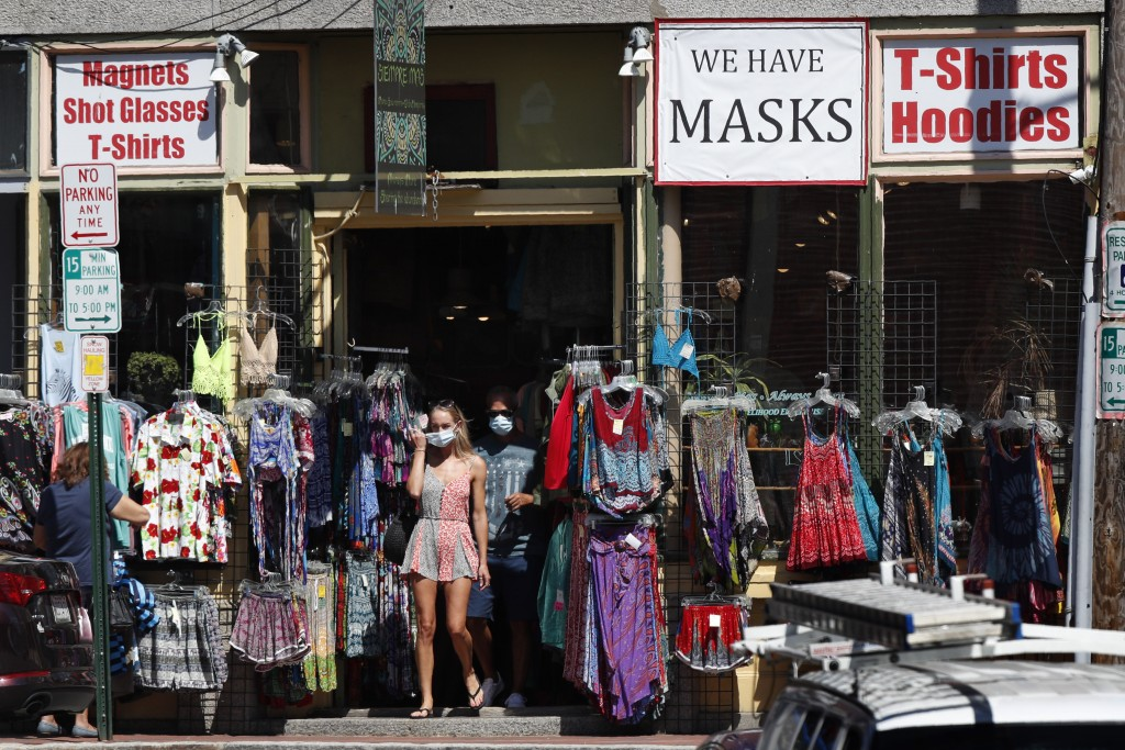 Shoppers leave a clothing shop that now also sells masks to help fight the spread of the coronavirus, Thursday, July 30, 2020, in Portland, Maine.   S...