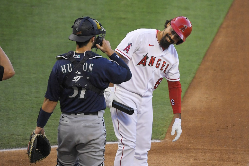 Los Angeles Angels' Anthony Rendon, right, smiles at Seattle Mariners catcher Joe Hudson after baseman Jose Marmolejos was unable to reach his foul ba...