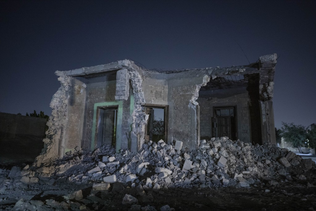A building stands partially demolished after bulldozers cleared the way for construction of a multilane freeway through the Northern Cemetery, part of...