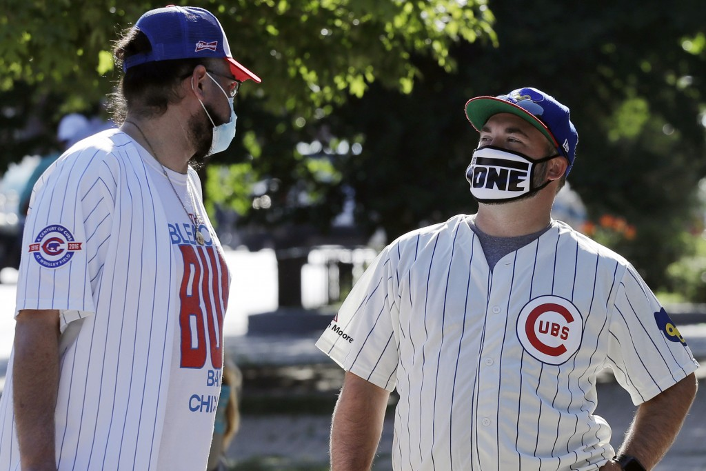 **Photo holds for Jordan Cohen's story** Chicago Cubs fans wait for a ball outside of Wrigley Field before the Opening Day baseball game between the C...
