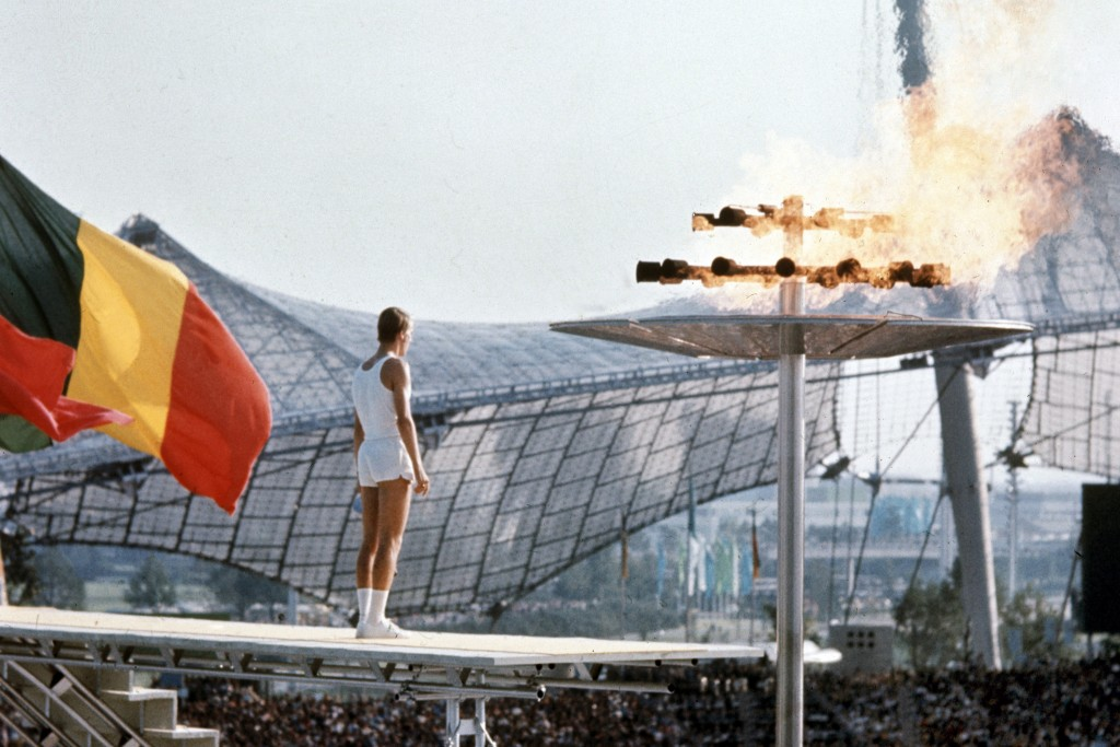 FILE - In this Aug. 26, 1972, file photo, West German middle distance runner, junior athlete Guenther Zahn (18), stands near the Olympic flame he lit ...