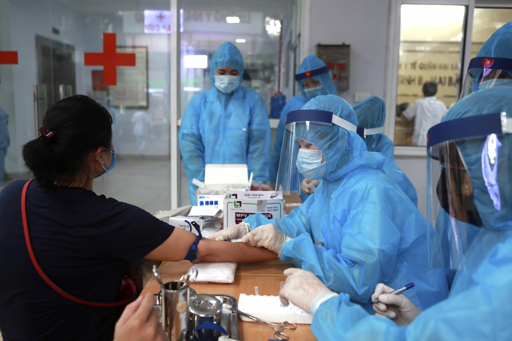 A health worker draws blood for COVID-19 test in Hanoi, Vietnam on Friday, July 31, 2020. Vietnamese state media on Friday reported the country's firs...