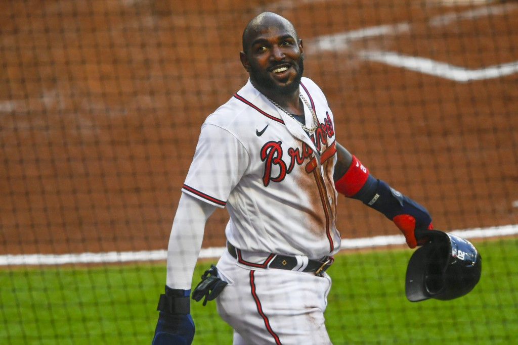 Atlanta Braves' Marcell Ozuna reacts as he walks to the dugout after scoring on a single line drive to right field by Dansby Swanson during the second...