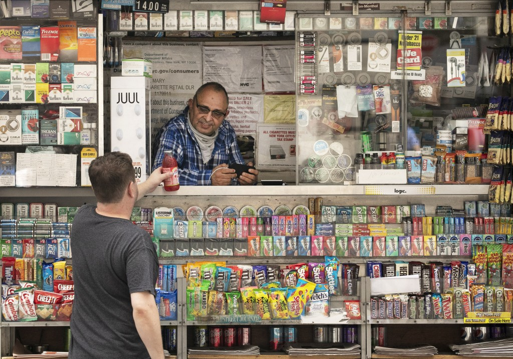 A man buys a cold drink at a news stand, Thursday, July 30, 2020, in New York. Stocks are falling on Wall Street Thursday after reports showed that la...