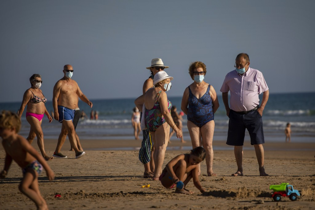 People wearing face masks gather at the beach in Barbate, Cadiz province, south of Spain, on Saturday, July 25, 2020. Ministers are set to remove Spai...