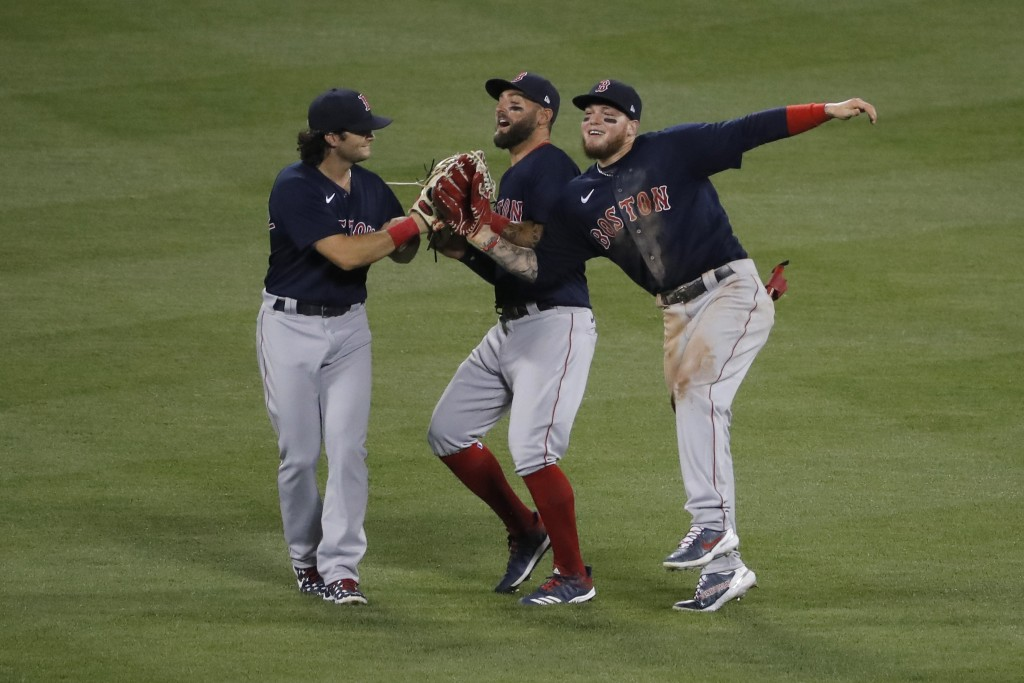 Boston Red Sox outfielders' Alex Verdugo, right, Kevin Pillar, center, and Andrew Benintendi celebrate after the baseball game against the New York Me...