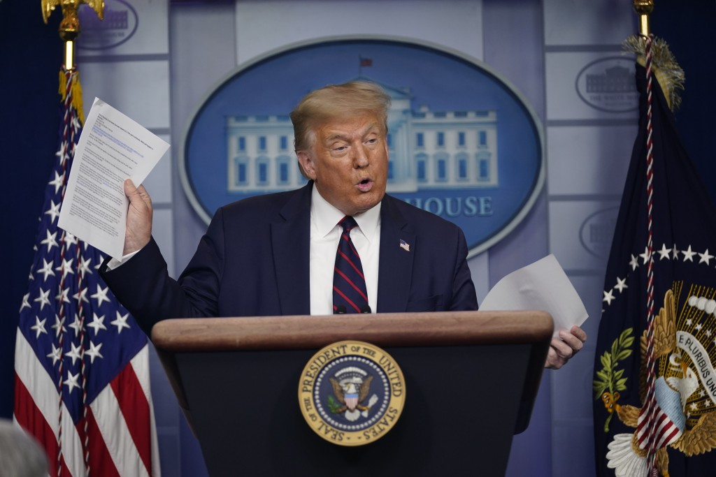 President Donald Trump holds articles as he speaks during a news conference at the White House, Thursday, July 30, 2020, in Washington. (AP Photo/Evan...