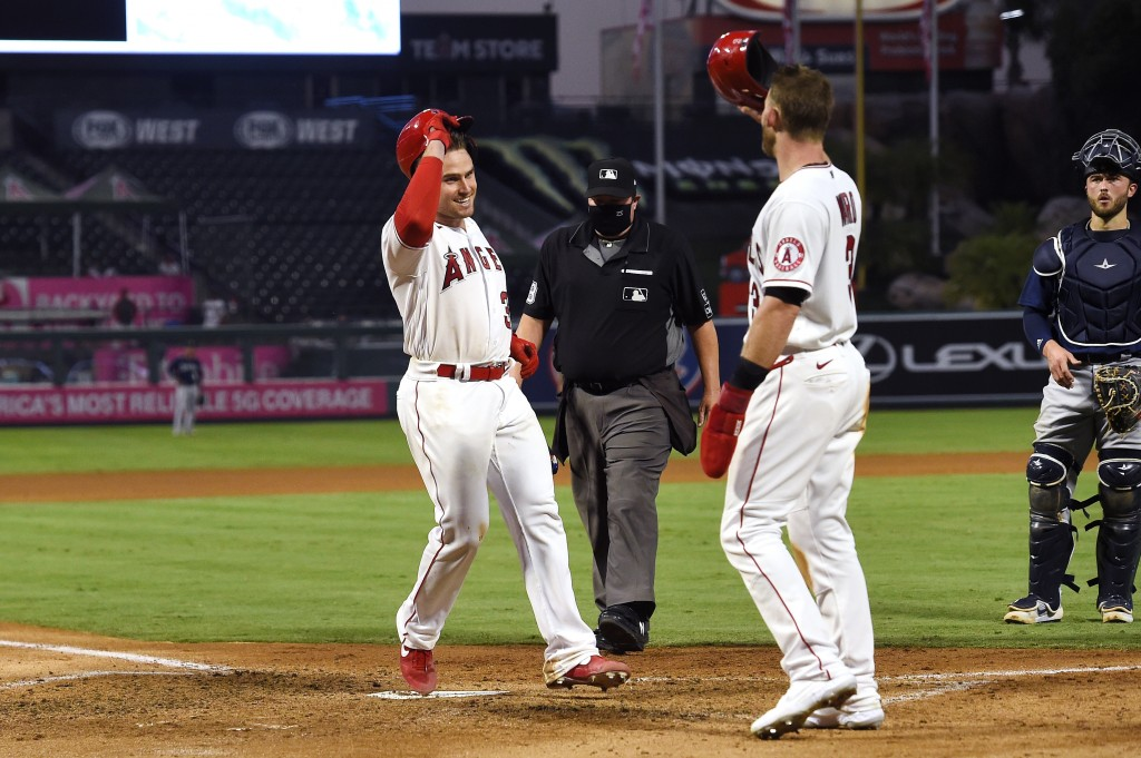 Los Angeles Angels' Max Stassi, left, touches home after hitting a two-run home run as Taylor Ward congratulates him while Seattle Mariners catcher Jo...