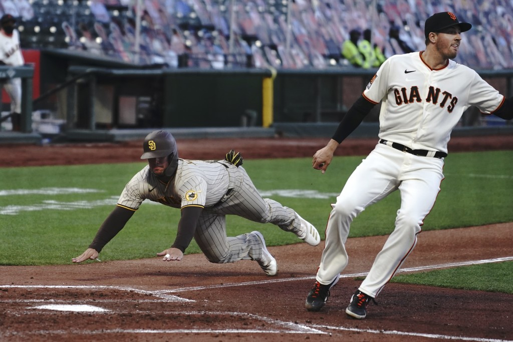 San Diego Padres' Ty France, left, slides into home to score past San Francisco Giants' Kevin Gausman during the third inning of a baseball game in Sa...