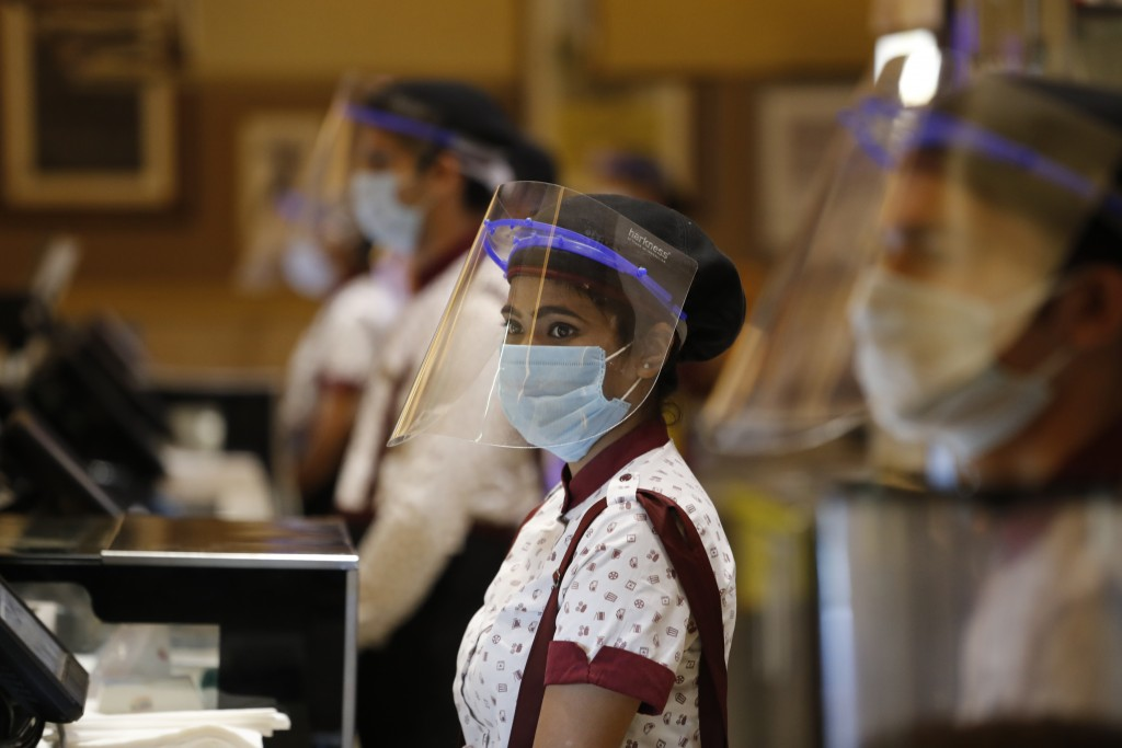 Workers of PVR cinemas, a multiplex cinema chain, stand at the food court with face shields and masks during a press preview to show their preparednes...