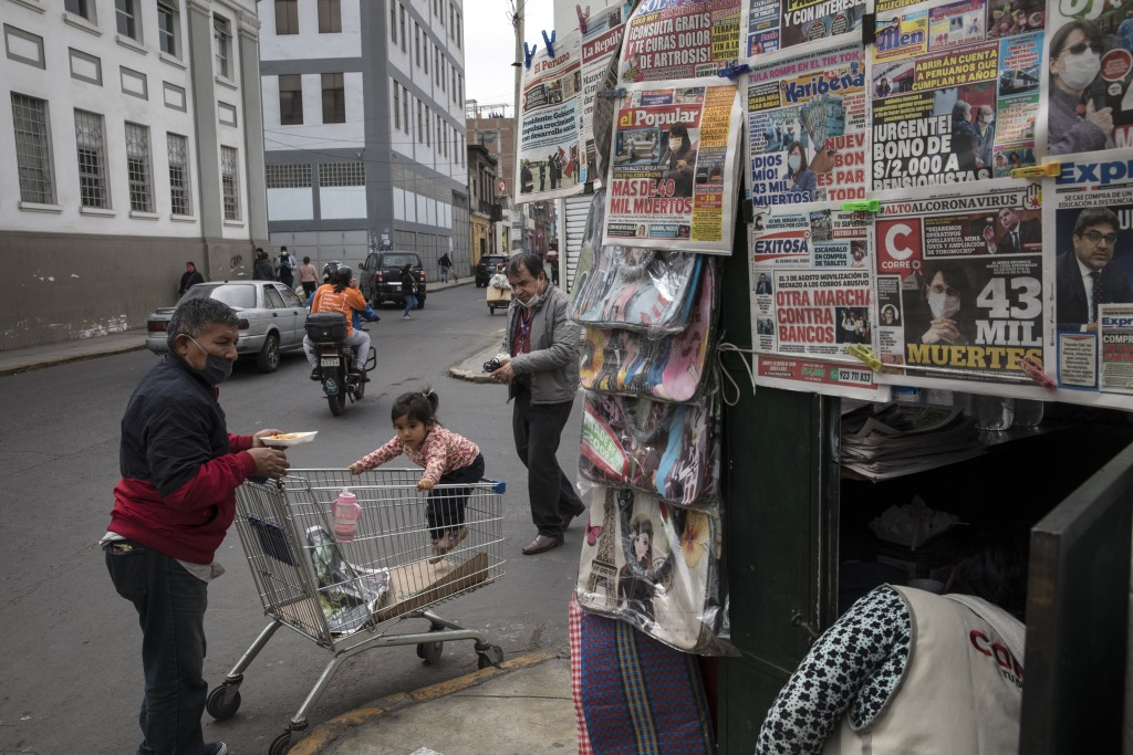 A man wearing a mask to curb the spread of the new coronavirus prepares to eat breakfast on a street in downtown Lima, Peru, Thursday, July 30, 2020. ...