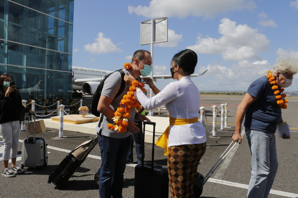 An airport officer, center right, welcomes a passenger on his arrival at Bali airport, Indonesia on Friday, July 31, 2020. Indonesia's resort island o...
