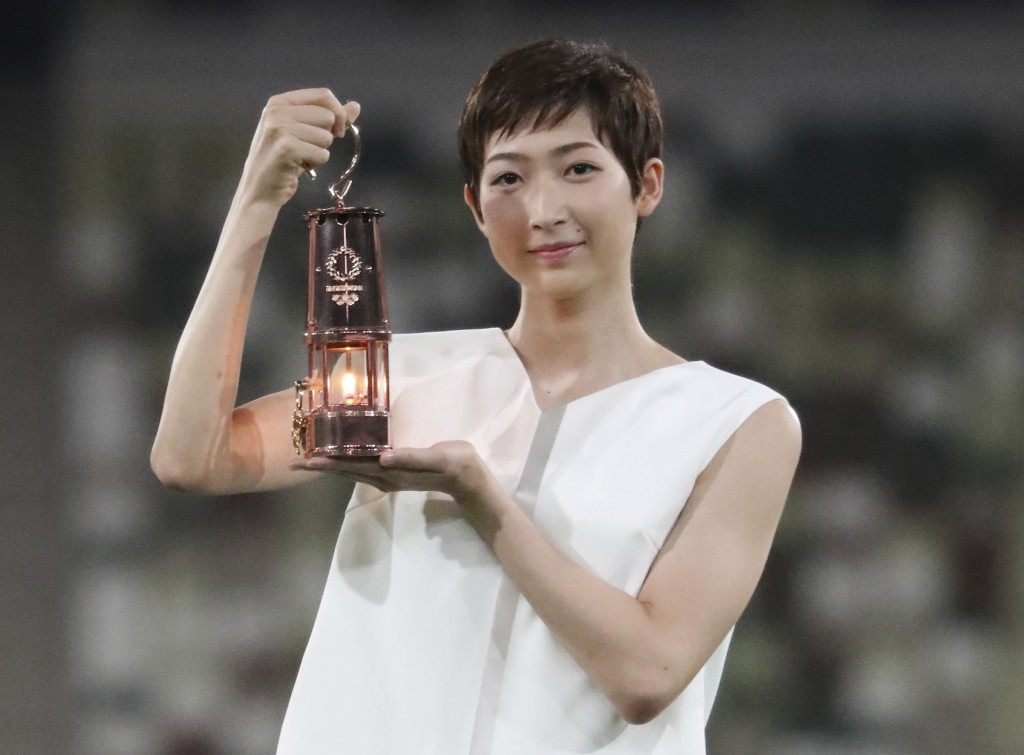FILE - In this July 23, 2020, file photo, Japanese swimming athlete Rikako Ikee holding the lantern containing Olympic flame poses during a photo sess...