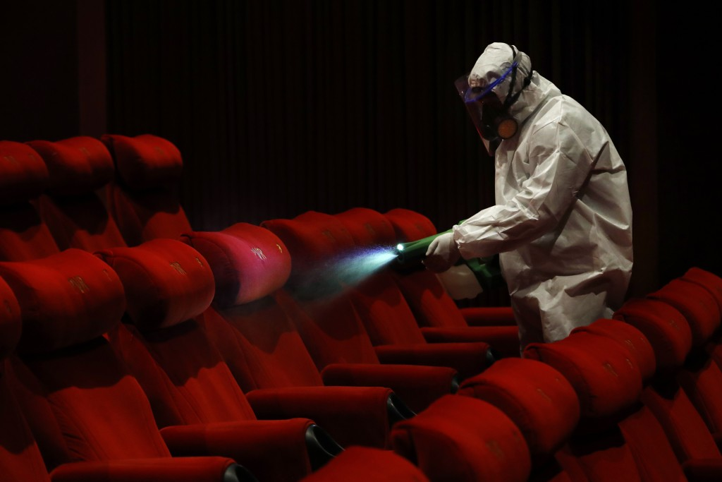 A worker of PVR cinemas, a multiplex cinema chain, sanitizes a hall during a press preview to show their preparedness with the COVID-19 pandemic in Ne...