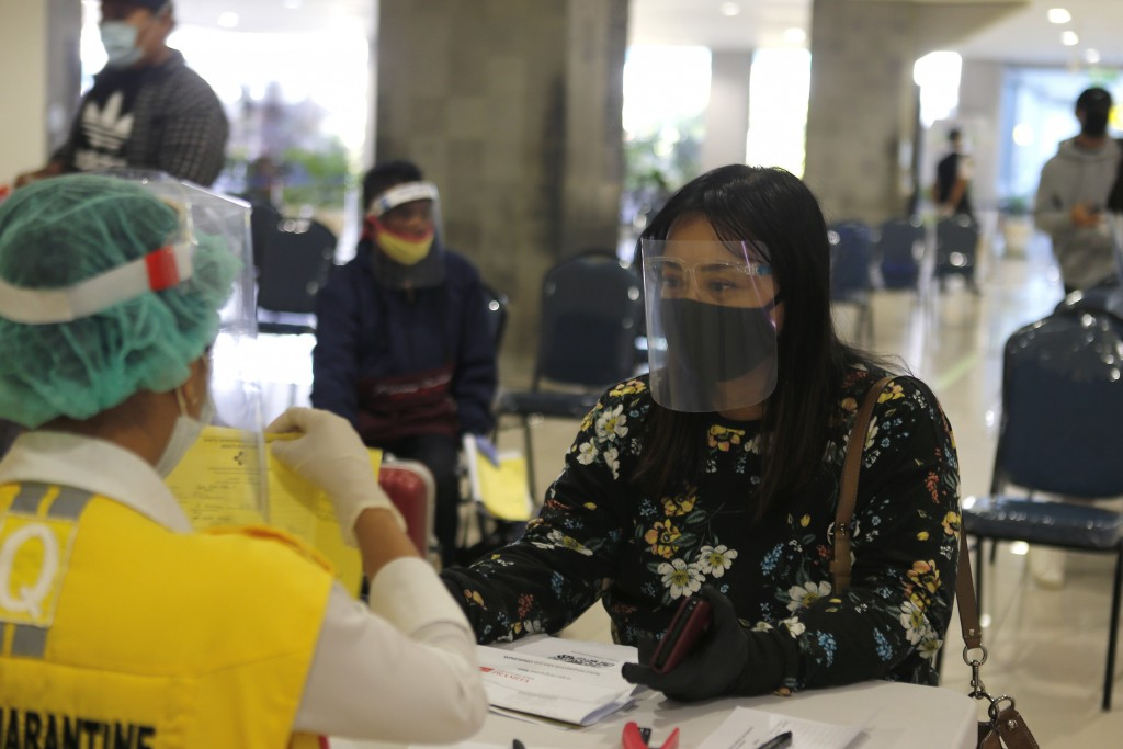 An officer checks passenger's health document on her arrival at Bali airport, Indonesia on Friday, July 31, 2020. Indonesia's resort island of Bali re...