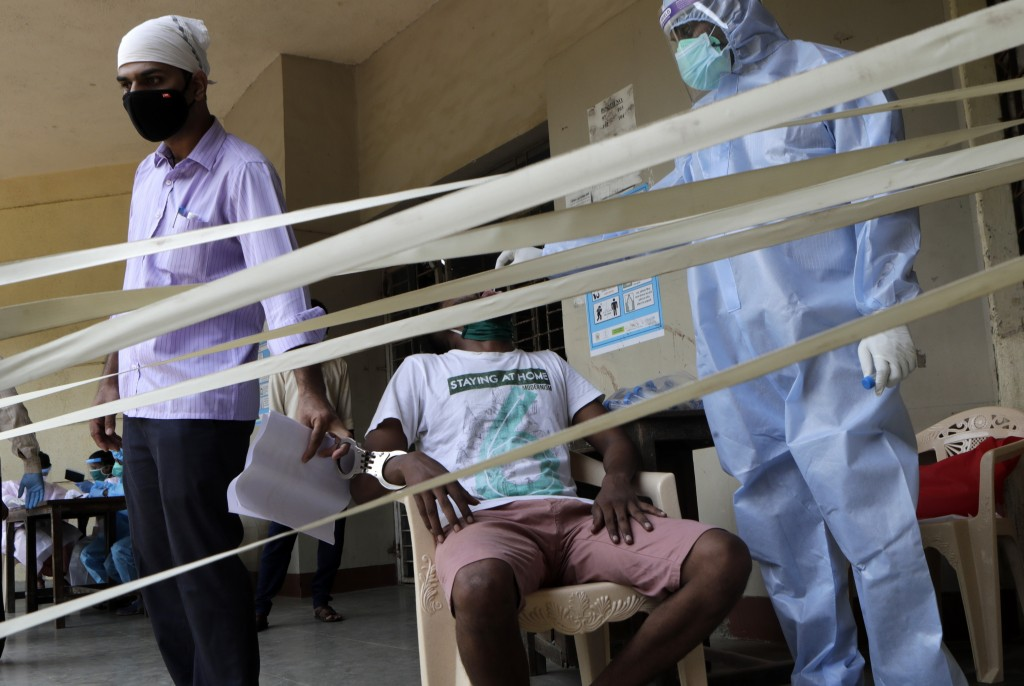 A policeman, left, stands guard as the swab sample of a prisoner is taken at a quarantine center in Mumbai, India, Friday, July 31, 2020. India is the...