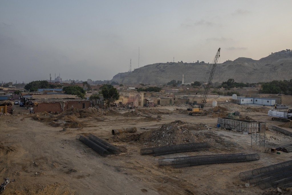 Construction work continues on a highway flyover in a portion cleared of graves in the City of Dead in Cairo, Egypt, with the Citadel, a medieval fort...