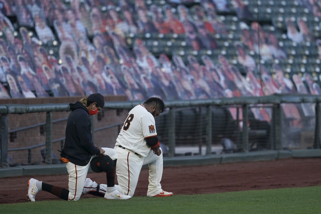 San Francisco Giants' Mauricio Dubon, left, and Pablo Sandoval kneel during the national anthem before a baseball game between the Giants and the San ...