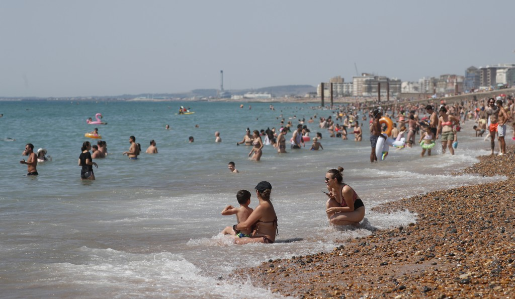 Beachgoers enjoy the sunshine and sea on what is now Britain's hottest day of the year so far, in Brighton, England, Friday, July 31, 2020. Temperatur...