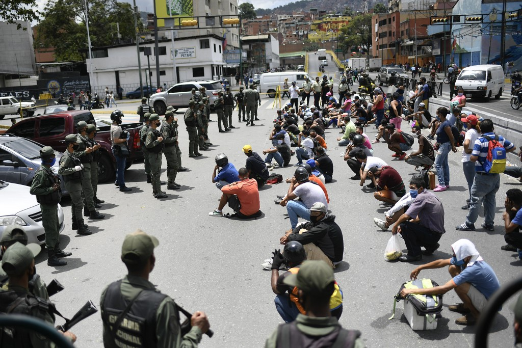 Members of the Bolivarian National Guarde explain proper mask use to non-compliant pedestrians and peddlers on a street of the Petare neighborhood of ...