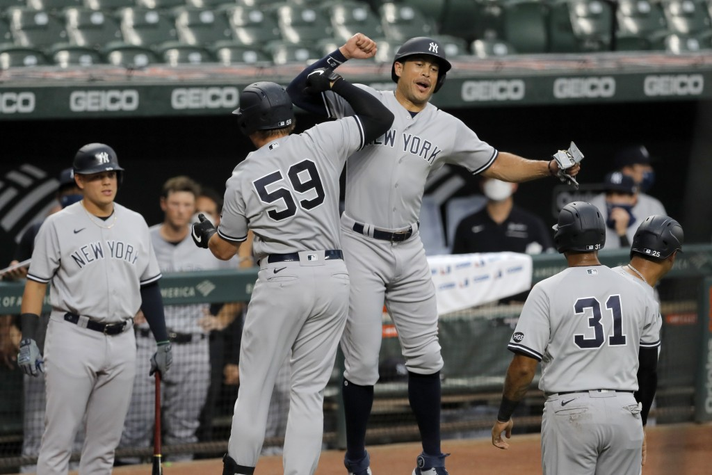 New York Yankees' Luke Voit (59) celebrates with Giancarlo Stanton, center right, after hitting a grand slam off Baltimore Orioles starting pitcher Jo...