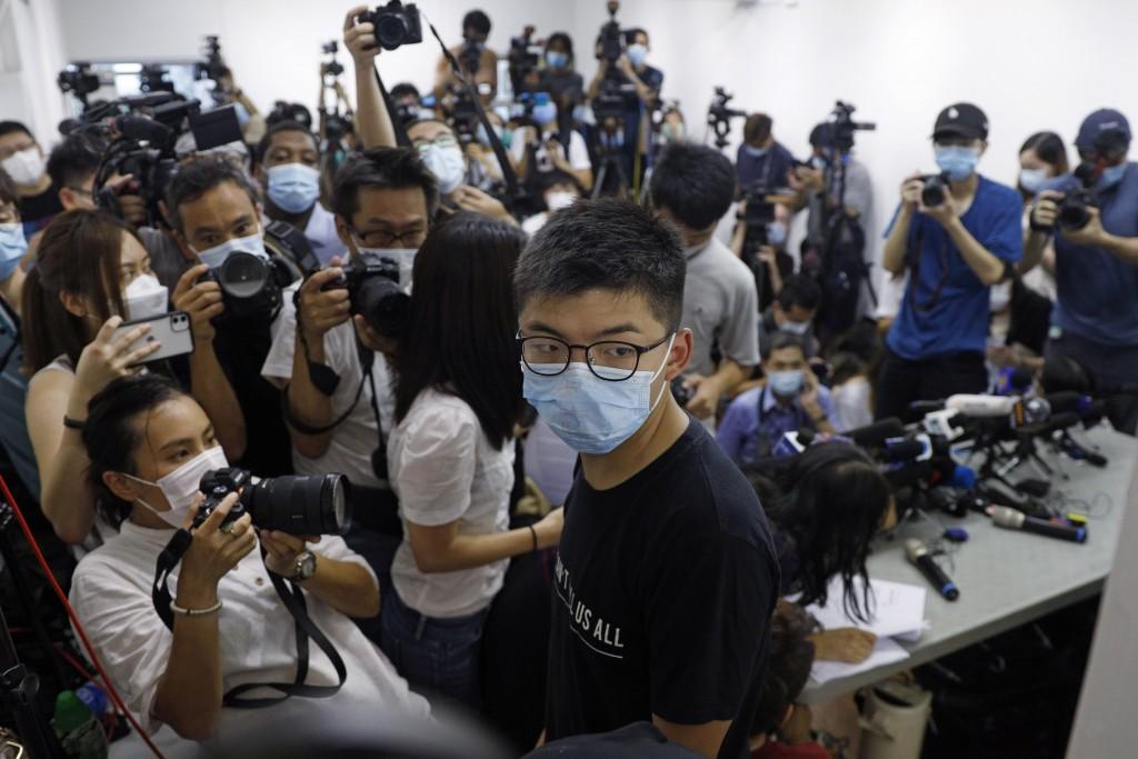Hong Kong pro-democracy activist Joshua Wong, center, attends a press conference in Hong Kong, Friday, July 31, 2020. At least 12 Hong Kong pro-democr...