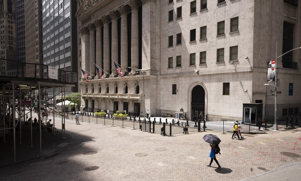 People pass the New York Stock Exchange, Thursday, July 30, 2020. Stocks are falling on Wall Street Thursday after reports showed that layoffs are con...