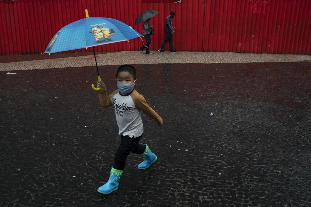 圖中為巴西里約一小男孩戴上口罩持雨傘走過人行道。(美聯社圖片)