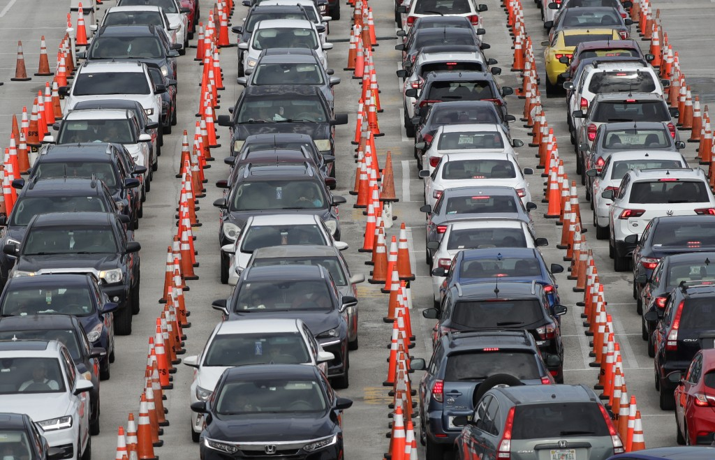 FILE - In this July 5, 2020, file photo, lines of cars wait at a drive-thru coronavirus testing site outside Hard Rock Stadium in Miami Gardens, Fla. ...