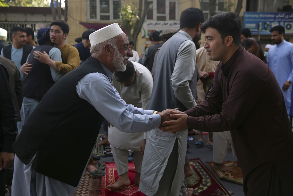 Afghan Muslims greet each other after offering Eid al-Adha prayers in Kabul, Afghanistan, Friday, July 31, 2020. During the Eid al-Adha, or Feast of S...