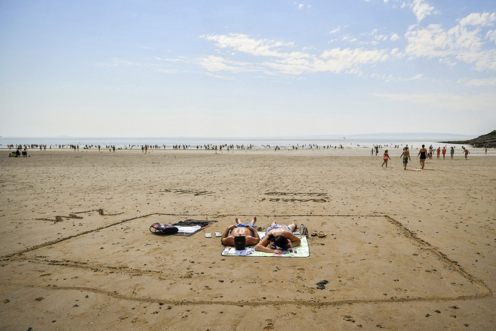 People sunbathe in a marked out square in the sand, indicating two meters, on Barry Island beach, in Wales, Friday, July 31, 2020. First Minister for ...