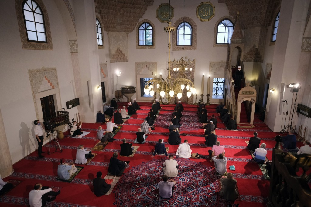 Worshippers wearing masks to help stop the spread of the coronavirus offer Eid al-Adha prayer while maintaining a social distance at the Gazi Husrev-b...