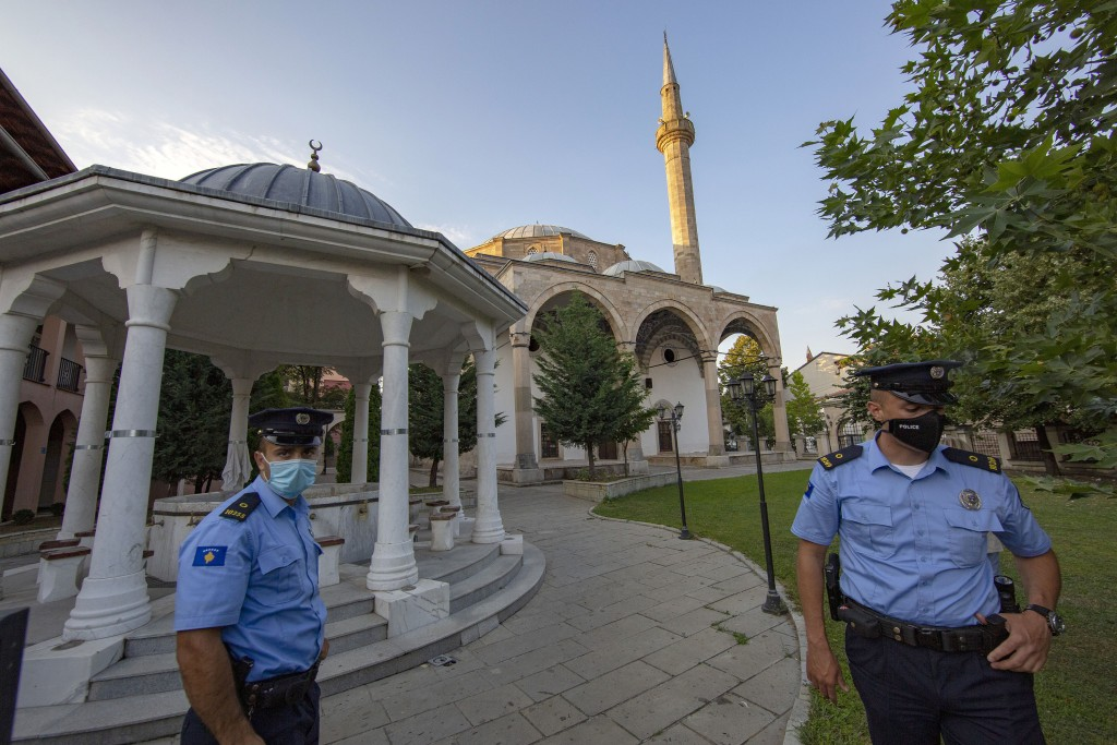 Kosovo police officers stand outside the Sultan Mehmet Fatih mosque in Pristina, Kosovo, Friday, July 31, 2020. Government measures banned all public ...