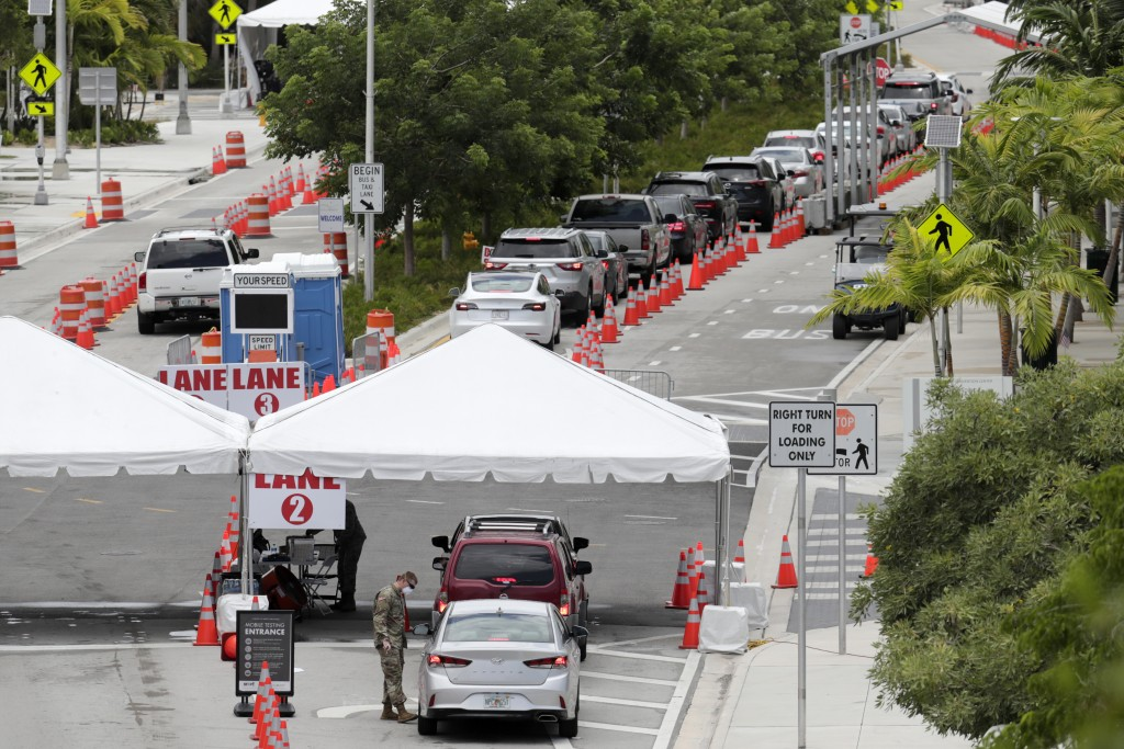 FILE - In this Sunday, July 12, 2020, vehicles wait in line at a COVID-19 testing site at the Miami Beach Convention Center during the coronavirus pan...