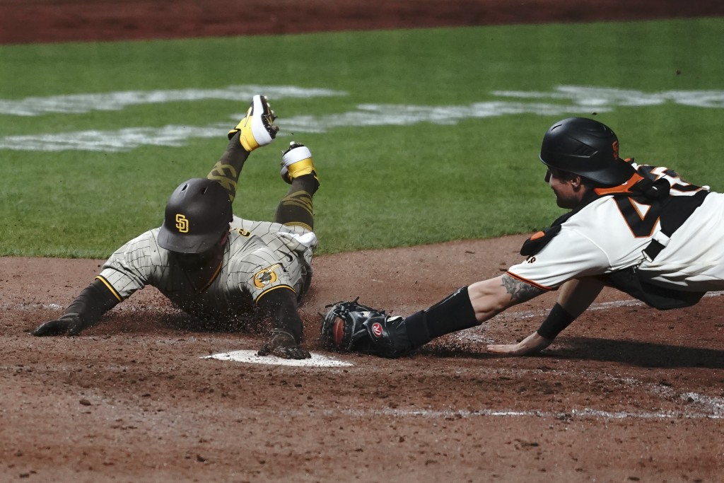 San Diego Padres' Greg Garcia, left, scores against San Francisco Giants catcher Tyler Heineman during the tenth inning of a baseball game in San Fran...
