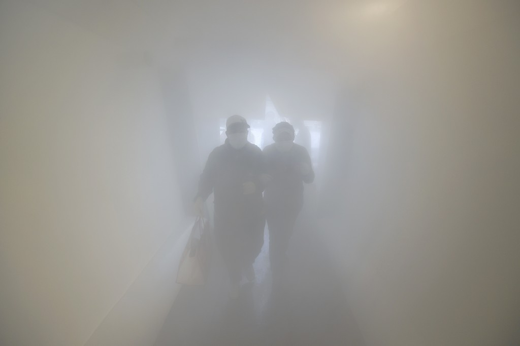 A couple wearing protective face masks walk through a decontamination chamber as a preventive measure against the spread of the new coronavirus, befor...