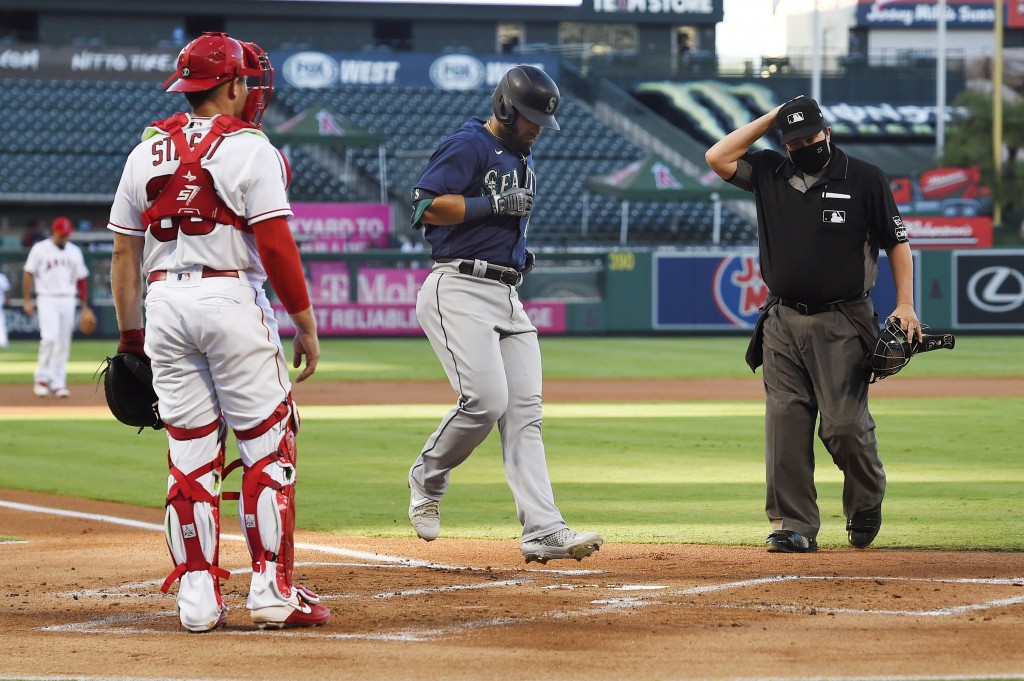Seattle Mariners' Jose Marmolejos, center, touches home after hitting a three-run home run as Los Angeles Angels catcher Max Stassi, left, watches alo...