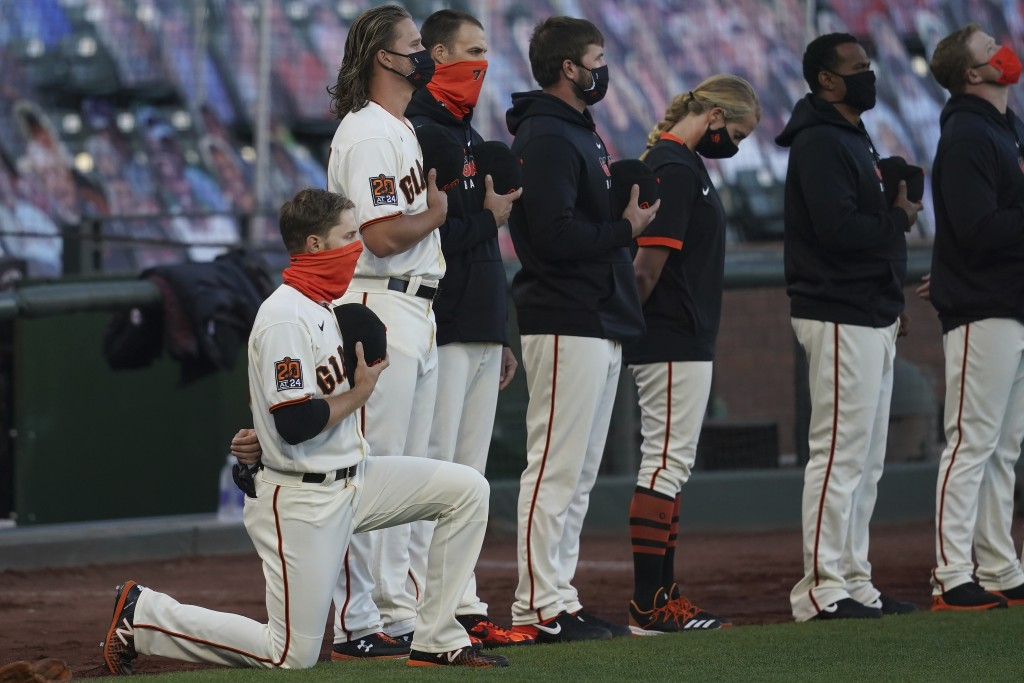 San Francisco Giants' Austin Slater, left, kneels during the national anthem before a baseball game between the Giants and the San Diego Padres in San...