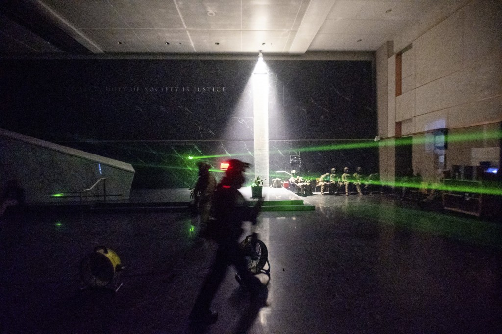 FILE - In this July 24, 2020, file photo, green lines cast by protesters' laser pointers cross the darkened lobby of the Mark O. Hatfield U.S. Courtho...