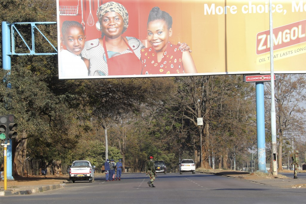 Armed soldiers patrol a street in Harare, Friday, July, 31, 2020. Zimbabwe's capital, Harare, was deserted Friday, as security agents vigorously enfor...