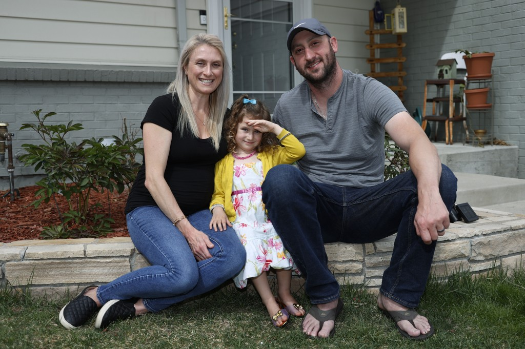 FILE - In this April 30, 2020, file photo, Eli Oderberg, right, sits with Katie Evers and their 4-year-old daughter, Everlee, outside their home in so...