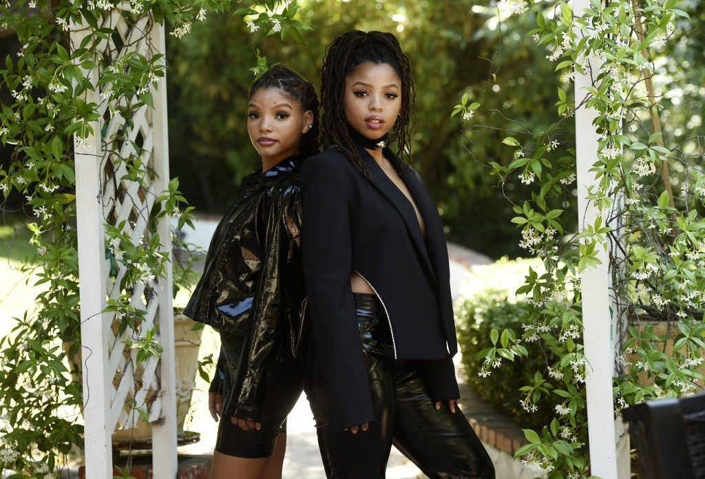 FILE - Halle Bailey, left, and her sister Chloe Bailey, of the R&B duo Chloe X Halle, pose for a portrait in their backyard in Los Angeles on May 28, ...