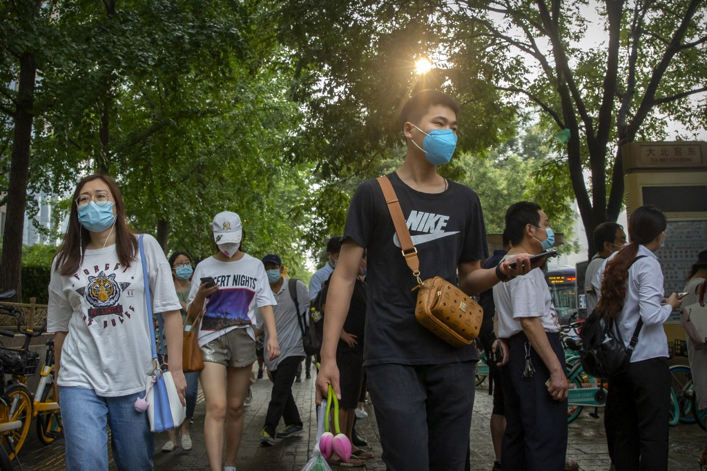 People wearing face masks to protect against the coronavirus walk along a street in Beijing, Friday, July 31, 2020. China is tightening travel restric...