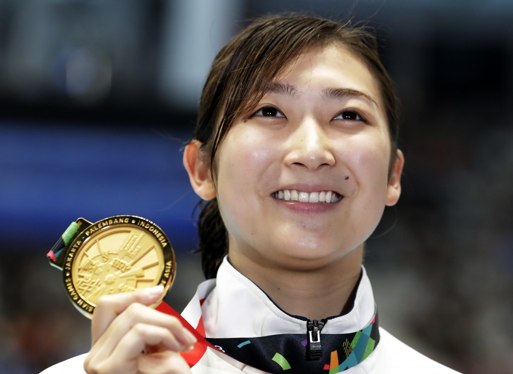FILE - In this Aug. 24, 2018, file photo, Japan's Rikako Ikee holds up her gold medal after winning the women's 50m freestyle final during the swimmin...