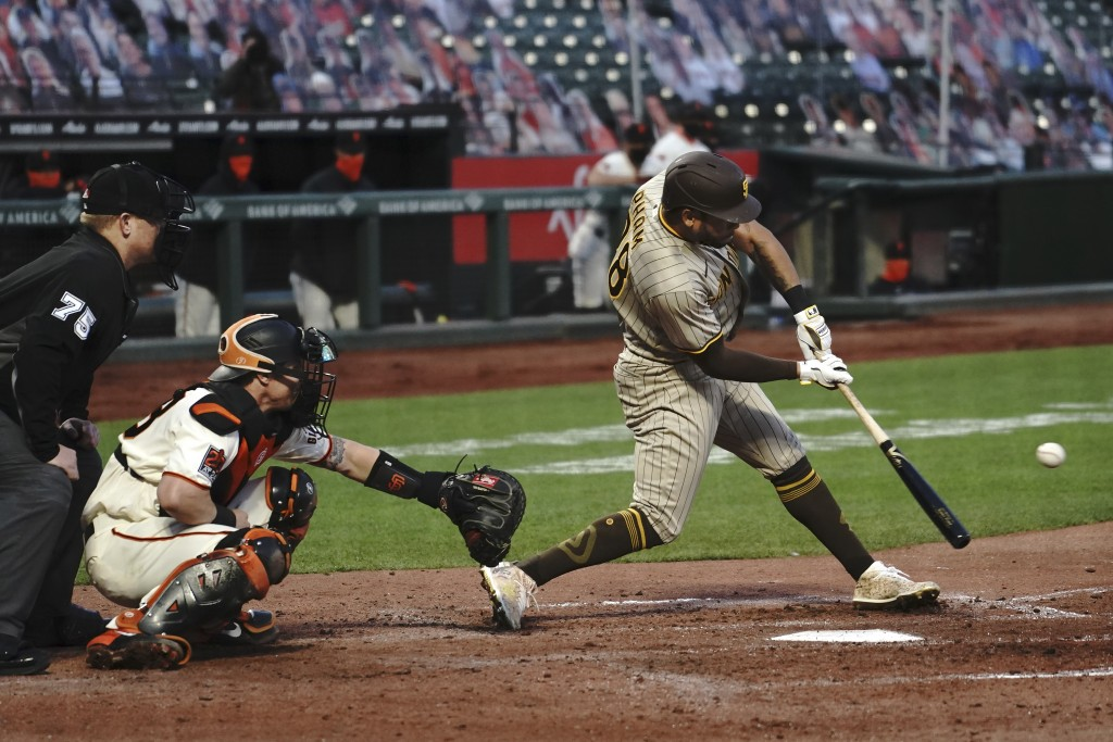 San Diego Padres' Tommy Pham, right, hits a run-scoring single in front of San Francisco Giants catcher Tyler Heineman, center, and umpire Tom Woodrin...